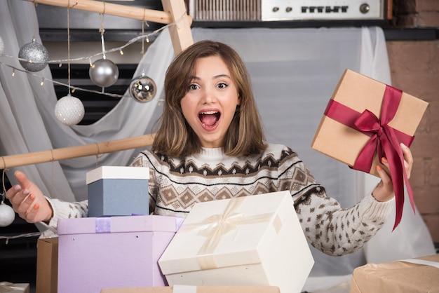 Mulher alegre segurando um presente de natal na sala de estar.