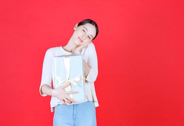 Mulher alegre segurando uma caixa de presente e um pé na parede vermelha