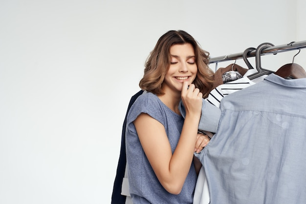 Mulher alegre seleção de roupas perto do fundo isolado do guarda-roupa