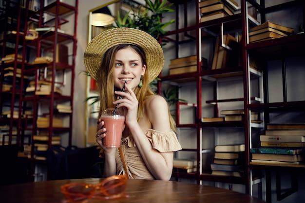 Mulher alegre sentada à mesa com uma bebida em uma recreação de café