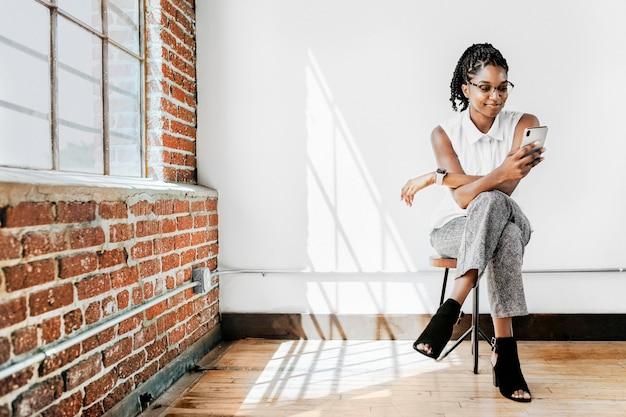 Mulher alegre sentada em uma cadeira usando o smartphone