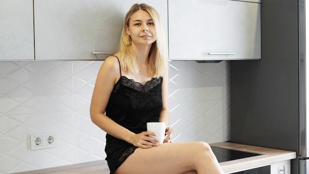 Mulher alegre sentada na bancada de uma cozinha moderna branca