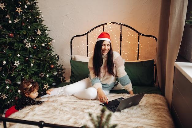 Mulher alegre sentada na cama enquanto olha para a tela do laptop enquanto uma criança está perto da árvore de natal