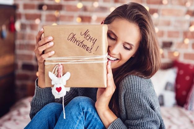 Mulher alegre sentada na cama segurando um presente