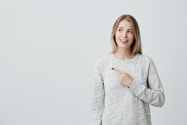 Mulher alegre sorridente apontando com o dedo na copyspace