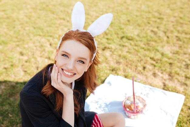 Mulher alegre sorridente com longos cabelos vermelhos usando orelhas de coelho
