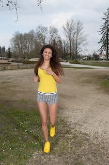 Mulher alegre sorridente correndo ao ar livre no parque