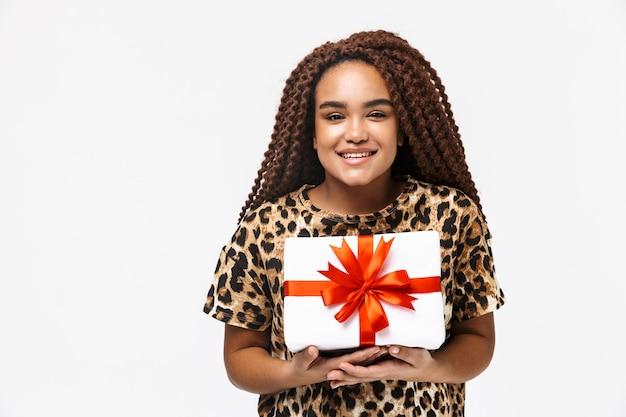 Mulher alegre sorrindo e segurando uma caixa de presente com um laço enquanto fica de pé, isolado contra uma parede branca
