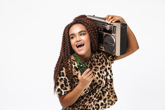 Mulher alegre, sorrindo e segurando uma caixa de som vintage com fita cassete no ombro, isolada contra uma parede branca