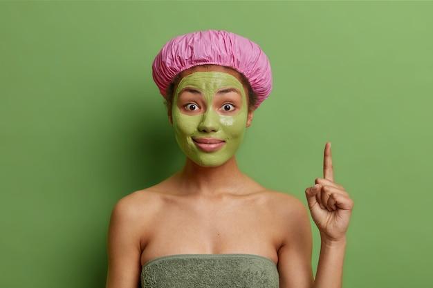 Mulher alegre surpresa aplica máscara nutritiva verde indica produto cosmético demonstrado acima, embrulhado em toalha de banho, usa chapéu de banho, tem ótima ideia, gosta de procedimentos de limpeza