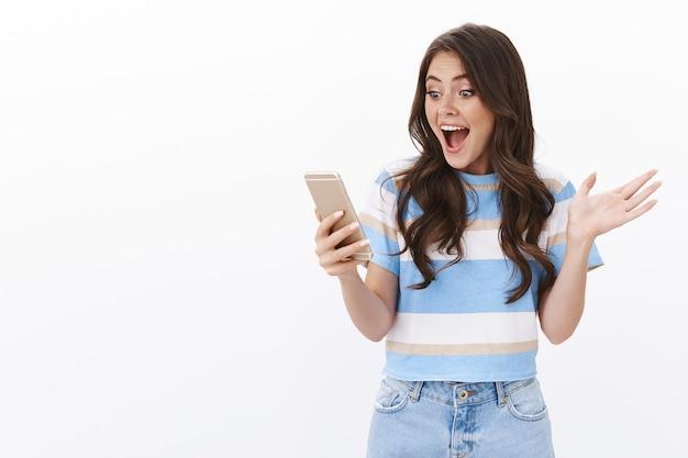 Mulher alegre surpresa e animada receber notícias agradáveis, ler mensagem sorrindo alegre, satisfeita, levantar a mão feliz, segurar smartphone satisfeito resultado incrível verificando pontuação online, parede branca