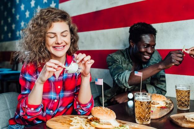 Mulher alegre, tendo um descanso no bar com o homem no café, conversando, rindo, comer fast-food.