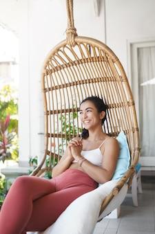 Mulher alegre, terna e feliz, com cabelo escuro encaracolado, aproveitando as férias sentado em uma cadeira de vime