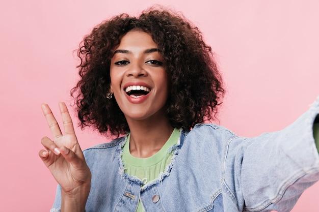 Mulher alegre tira uma selfie e mostra o símbolo da paz na parede rosa