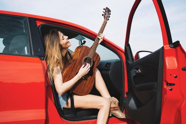 Mulher alegre tocando violão em carro vermelho
