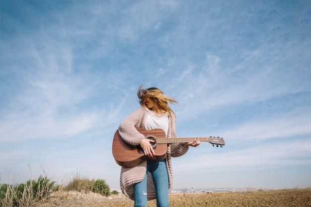 Mulher alegre tocando violão no campo Foto gratuita
