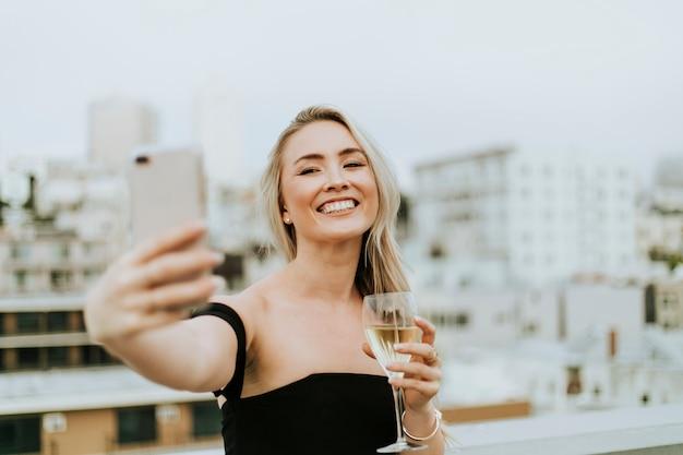 Mulher alegre tomando uma selfie em uma festa na cobertura