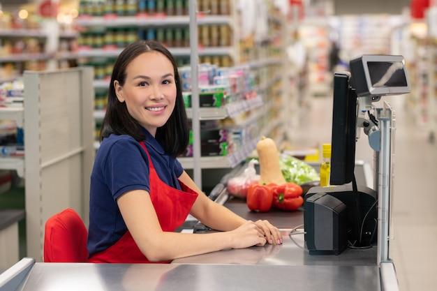 Mulher alegre trabalhando em um supermercado, sentada no caixa