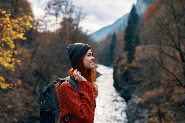 Mulher alegre turista de todas as leis admira a natureza do rio da montanha