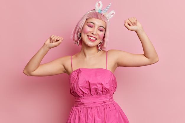 Mulher alegre usa peruca rosa levanta os braços dança despreocupada fecha os olhos de satisfação sorri suavemente usa vestido festivo com tiara de unicórnio