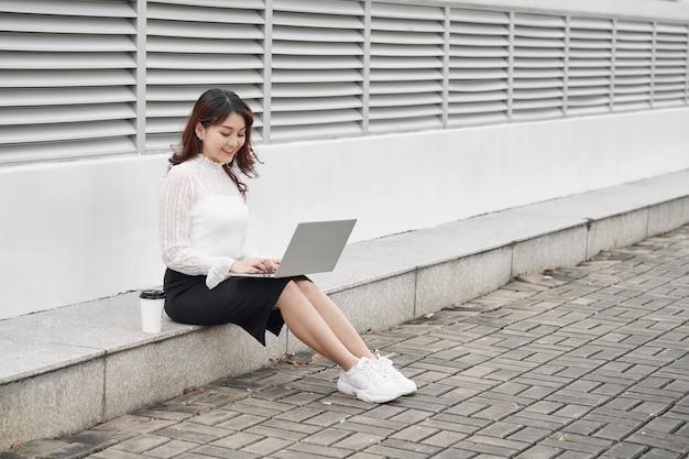 Mulher alegre usando laptop sentada nas pegadas