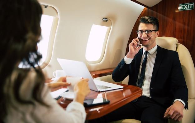 Mulher alegre, usando óculos e trajes formais, que está digitando algo em seu laptop e falando ao telefone, voando na classe executiva com seu colega.