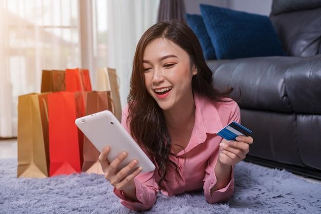 Mulher alegre usando tablet digital para compras on-line com cartão de crédito na sala de estar
