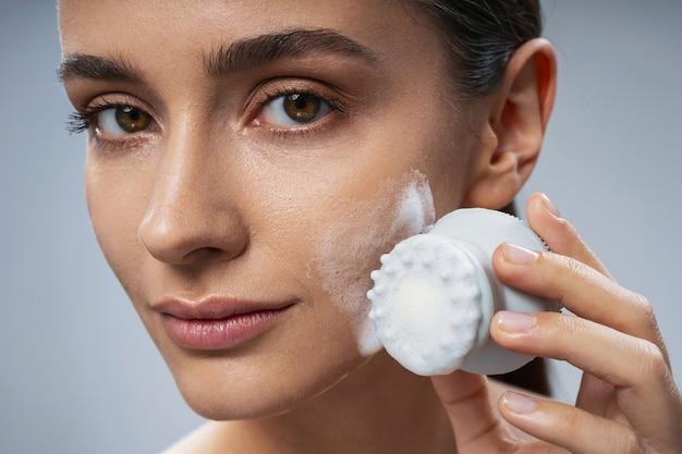 Mulher alegre usando uma almofada de peeling para limpar a pele