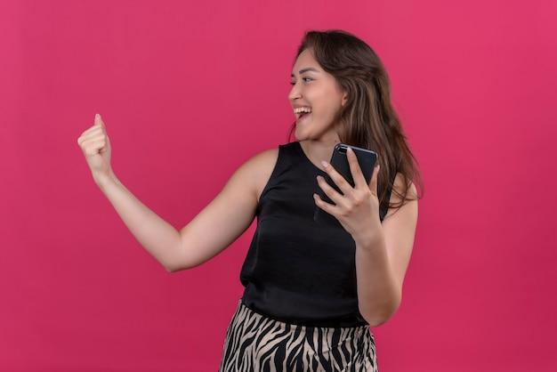 Mulher alegre vestindo camiseta preta ouvindo música no telefone e dançando na parede rosa