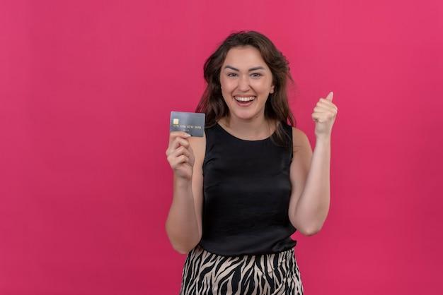 Mulher alegre vestindo camiseta preta segurando um cartão de crédito na parede rosa