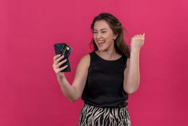 Mulher alegre vestindo camiseta preta segurando um telefone e um cartão do banco na parede rosa
