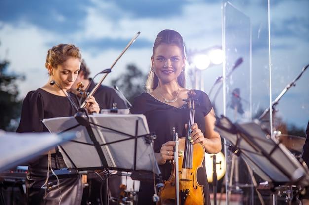 Mulher alegre violinista tocando orquestra ao ar livre