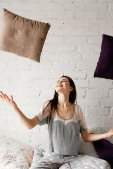 Mulher alegre vomitando travesseiros.