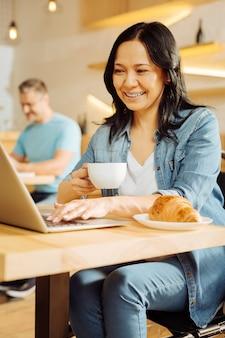 Mulher aleijada de cabelos escuros bem alerta, sentada em uma cadeira de rodas, segurando uma xícara de café, trabalhando em seu laptop e um homem sentado ao fundo