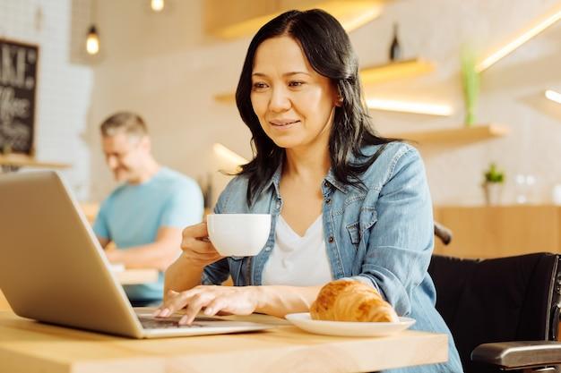 Mulher aleijada de cabelos escuros muito alegre sentada em uma cadeira de rodas, segurando uma xícara de café e trabalhando em seu laptop e um homem sentado ao fundo