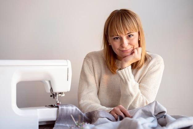 Mulher alfaiate de vista frontal usando máquina de costura
