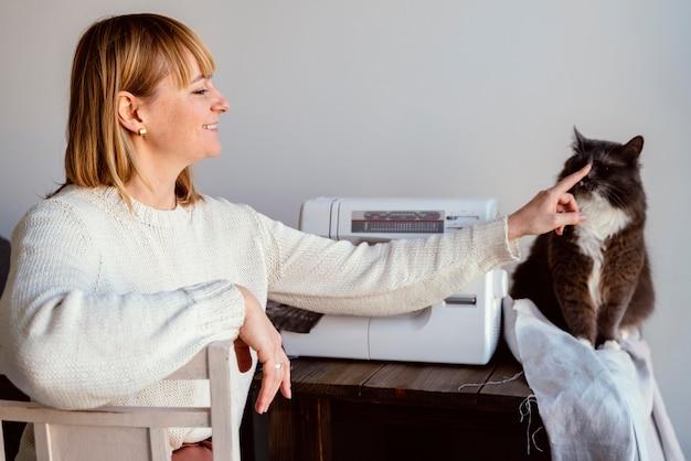 Mulher alfaiate e vista frontal do gato