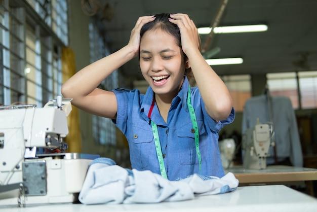 Mulher alfaiate segura a cabeça devido ao estresse de costurar mal as roupas da sala de produção