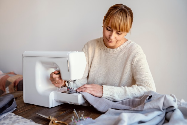 Mulher alfaiate usando máquina de costura Foto gratuita