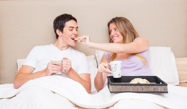 Mulher, alimentação, biscoitos, para, dela, namorado, sentar-se cama