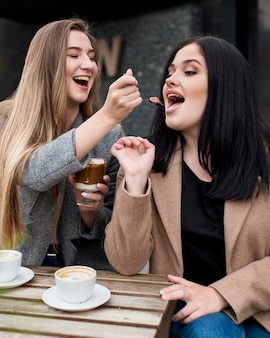 Mulher alimentando a amiga com a sobremesa