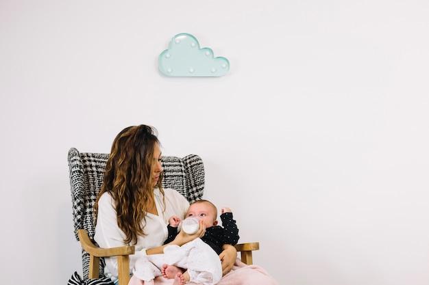 Mulher alimentando bebê sob nuvem