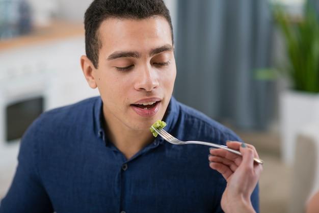 Mulher alimentando o namorado em um jantar romântico