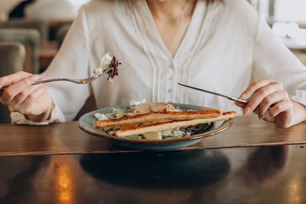 Mulher almoçando em um café, comendo salada de perto