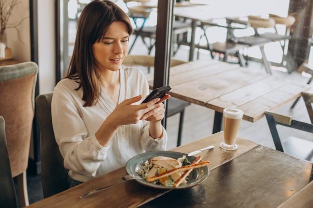Mulher almoçando em um café, comendo salada