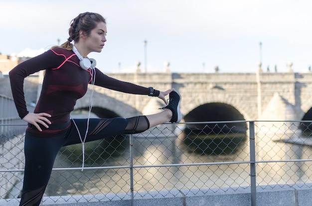 Mulher alongamento descansando depois de correr e correr em um parque com roupas esportivas