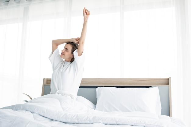 Mulher alongando-se depois de acordar de manhã.