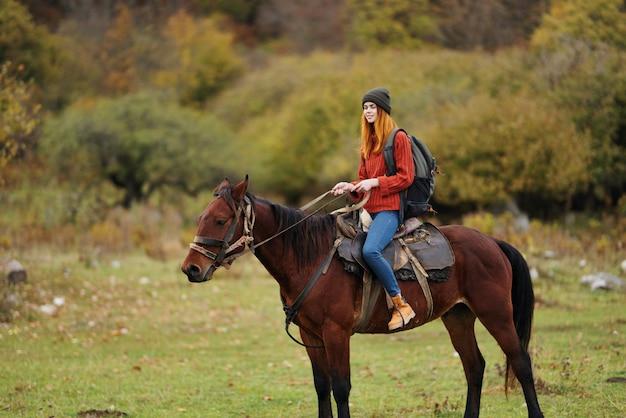 Mulher alpinista andando a cavalo em viagem pela natureza