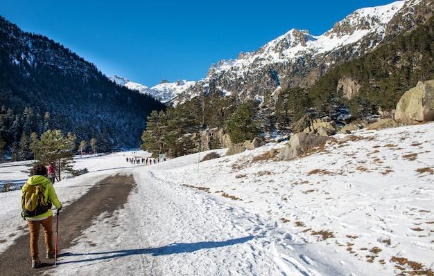 Mulher alpinista andando nas montanhas nevadas dos pirinéus