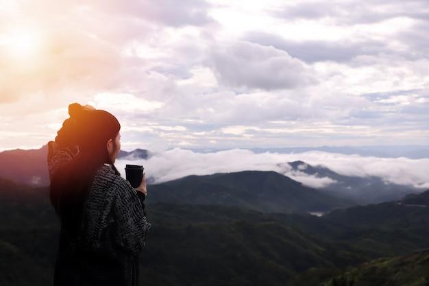 Mulher alpinista bebendo café quente com vista panorâmica na manhã, vista de temporada de inverno.